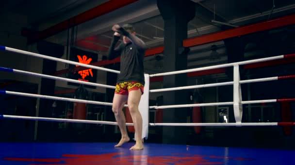 Muay Thai Boxer trainiert Schläge und Tritte im Boxring im städtischen Fitness-Studio. Schattenkampf. Boxsäcke dunkler Hintergrund