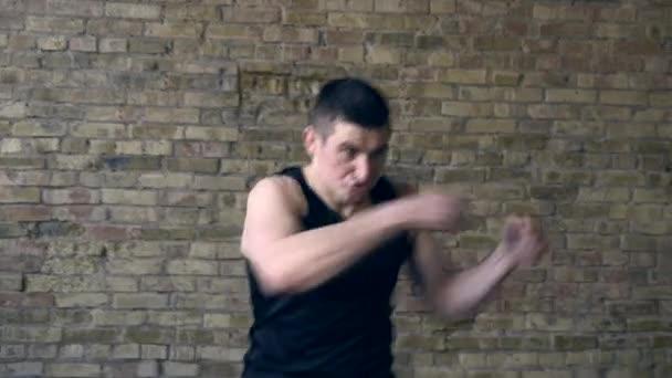 Muay Thai Boxer trainieren im Studio Schläge und Tritte. Schläge in der Luft mit Händen und Beinen. Backsteinmauer Hintergrund. Japanische Wörter auf der Malerei: Seele (oder Geist) des Kriegers (oder Samurai))