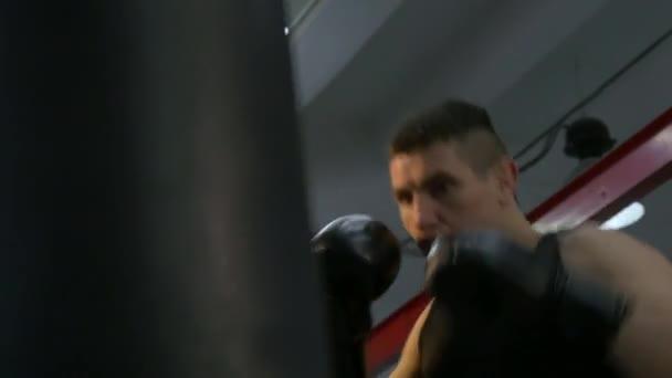 Close-up-Muay-Thai-Boxer Tritte und Schläge Boxsack. Kaukasischen Mann Training In städtischen Turnhalle