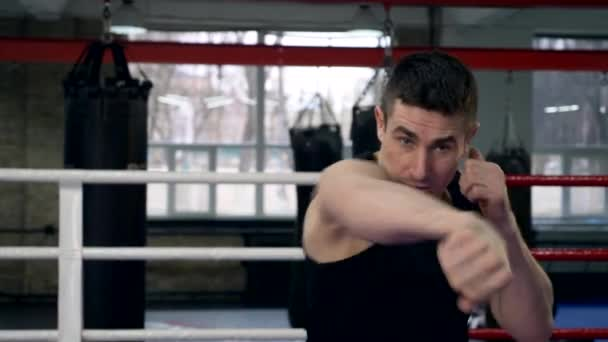 Slow-Motion Kämpfer Schläge In der Kamera. Muay Thai-Boxer im Ring Schatten Boxkampf Training. Boxsäcke im Fitness-Studio-Hintergrund