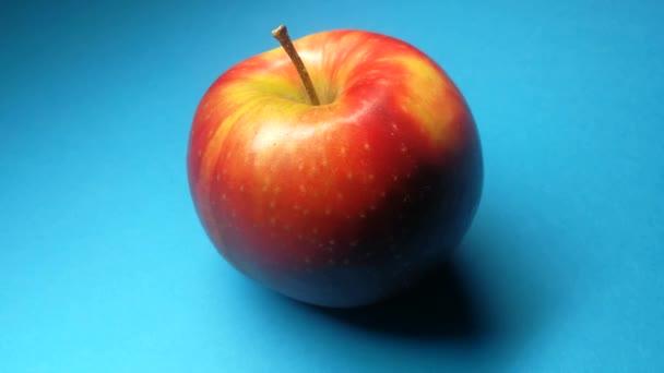 Červené jablko na modrém pozadí close-up.