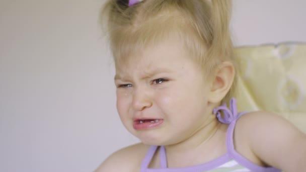 Una piccolo dolce bambina sta piangendo. Lacrime scorrono lungo le sue guance. Adorabile bambino gridante