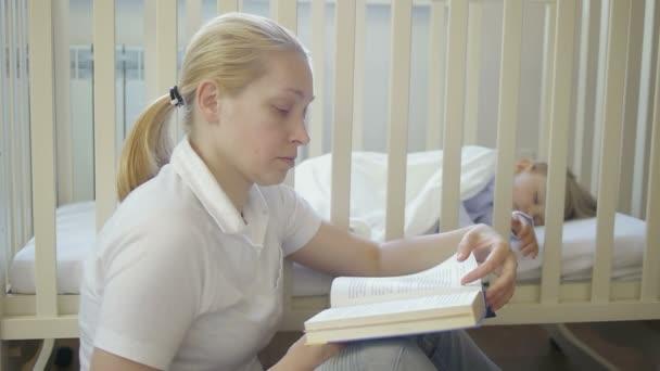 Dospělé ženy čte knihu sedí vedle spící děťátko v dětské postýlce