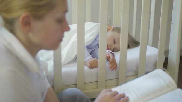 An adult woman reads a book sitting next to a sleeping little baby in a baby crib