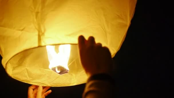 Close-up of male hands releasing Chinese lanterns in the night sky