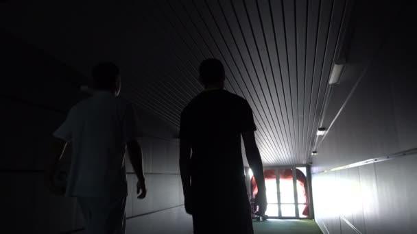 Dva hráče Fotbal jdou podél temným tunelem na fotbalové hřiště. Pohled z zadní