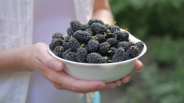 A woman is holding a bowl with an apetitic ripe tasty mulberry