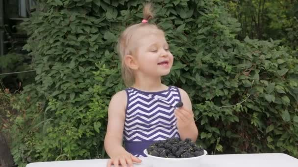 A cute little girl eats fresh mulberry with pleasure