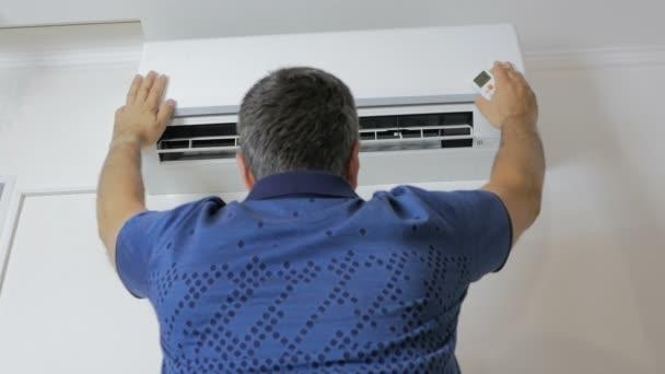 Der Mann steht unter der laufenden Klimaanlage und kühlt