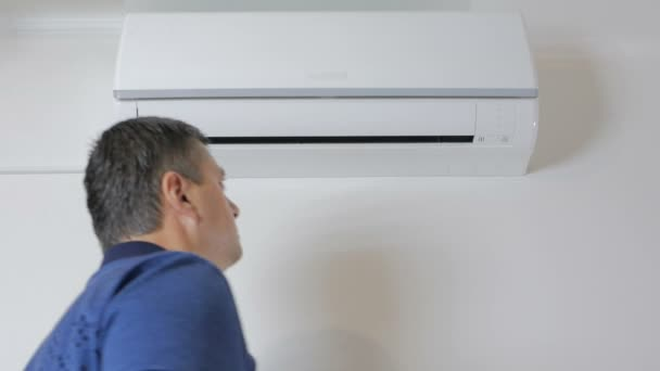 der Mann nähert sich der Klimaanlage und schaltet sie mit der Fernbedienung ein