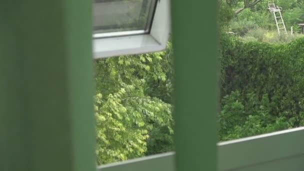 Pohled z okna polovina nechráněný prostřednictvím rozvojového rolety do deště a větru
