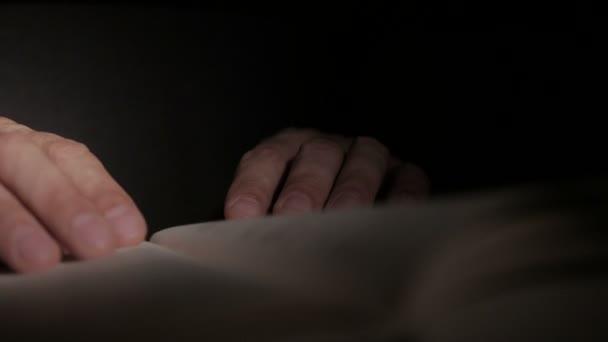 Nahaufnahme von einem mans Hand hält eine offene Papierbuch, mit seinen Fingern blätterte
