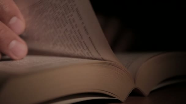 Nahaufnahme eines Mannes, der ein aufgeschlagenes Papierbuch in der Hand hält und die Seiten mit seinen Fingern umblättert