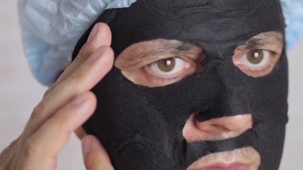 A close-up of the face of a man, 45 years old, applying a rejuvenating cosmetic mask of black tissue to the face and stroking his face