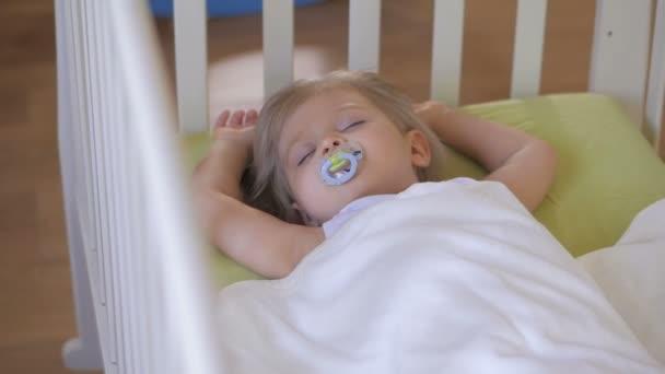 Egy kislány alszik a baba kiságy a cumi a szájába