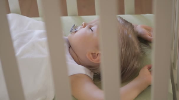 A little girl is sleeping in a baby crib with a pacifier in her mouth