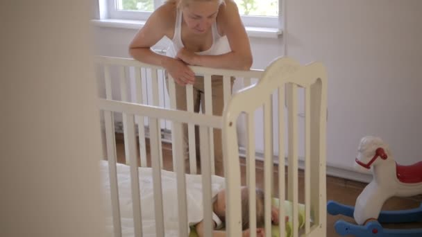 A woman stands at a baby crib and admires her little sleeping baby