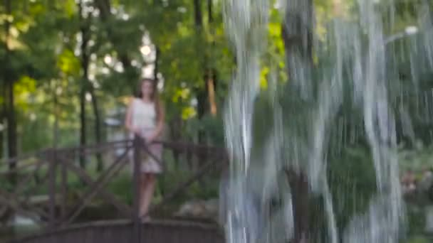 A girl walking in a park on a bridge looking at the pouring water from a fountain