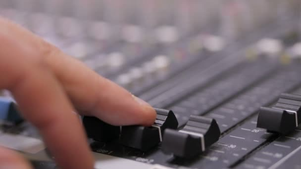 Hands of Audio engineer working on a professional analog console, moving faders, mixing music