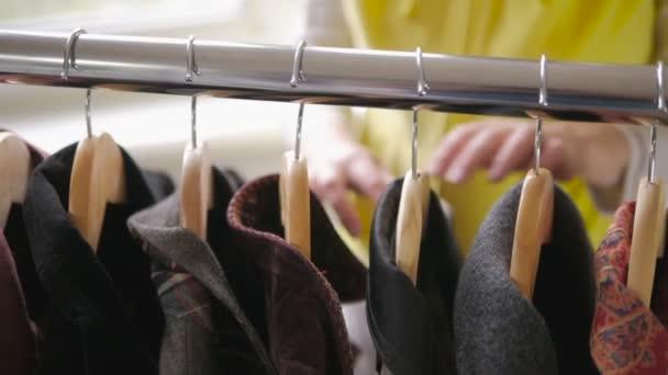 Detail z ženských rukou utrhl závěs s oblečením.