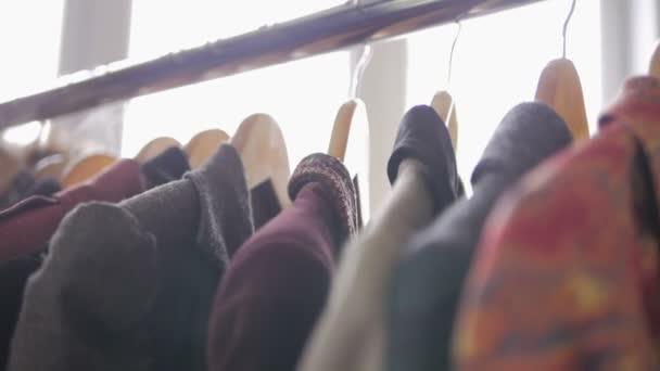 Detail z ženských rukou utrhl závěs s oblečením. Mnoho oblečení dámské zavěšení na ramínko