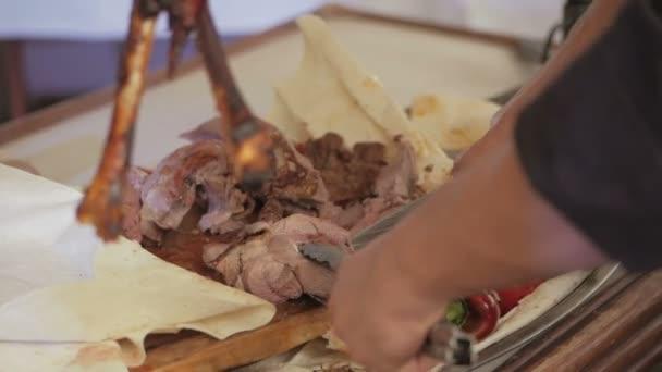 Kuchařka dělené jatečně upravených těl ovcí, pečené s ohněm s nožem