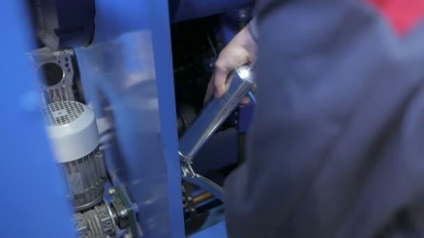 Worker in blue uniform customizing factory equipment