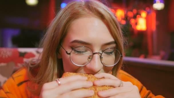 Mladá dívka v tygr kostým jí hamburger při posezení v kavárně