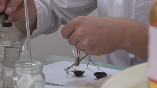 Pharmacist measuring the weight of drugs in a pharmacy using small old scales.