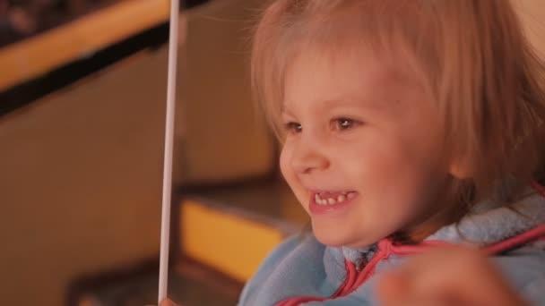 Malá holčička pozorně sleduje a směje se během představení cirkusu.