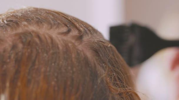 Žena rozjasní její kořínky vlasů na domácí použití bělicí olej s kartáčem.