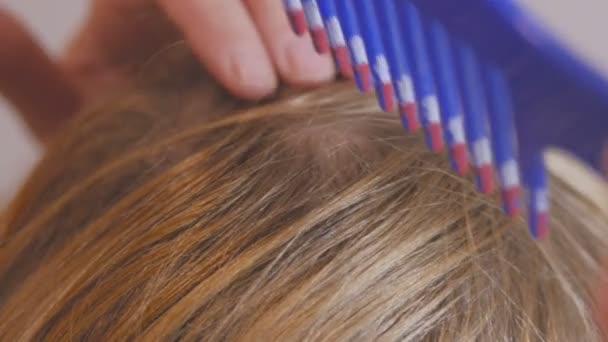Blondýnka s dlouhými vlasy je česání před zrcadlem, příprava hlavu k obarvení vlasové kořínky.