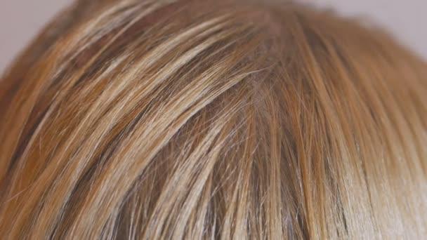 eine blonde Frau mit langen Haaren kämmt sich vor einem Spiegel und bereitet ihren Kopf darauf vor, Haarwurzeln zu färben.