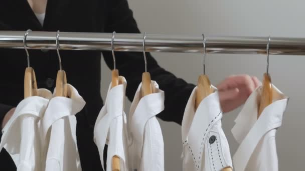Žena v černém kabátku zvolí bílé košile visí na ramínko do skříně nebo úložiště