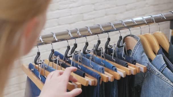 Detail z ženské prsty dotýká oblečení, na ramínko v obchodě nebo šatní skříň