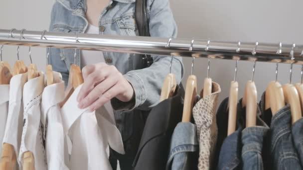 Žena v obchodě vybere oblečení a ukradne ji diskrétně, jejich uvádění v sáčku