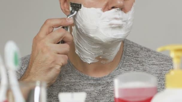 Egy ember, egy fürdőszoba tükör előtt shaves arcát borított fehér hab