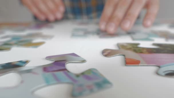 A man collects large puzzles on the table in the apartment