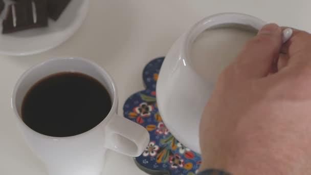 Muž nasype lžička cukru z cukřenky do šálku kávy