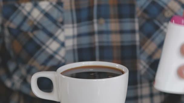 Muže, který seděl u stolu místo cukru přidává sladidlo do kávy
