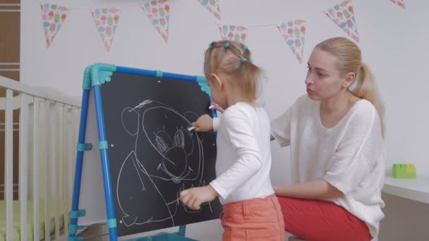 Mom teaches little girl to draw with chalk on a blackboard.
