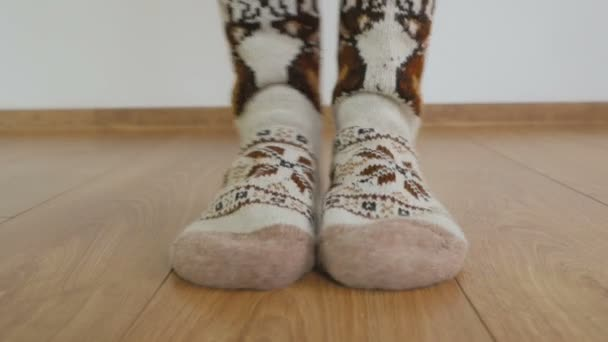 Close-up of the legs of a woman in warm wool socks are standing on the wooden floor in the room and trampling