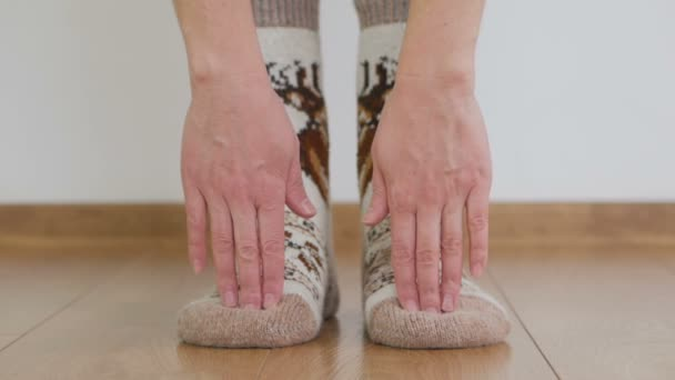 Woman in warm woolen socks doing gymnastics bends down, touching the floor with her fingers.