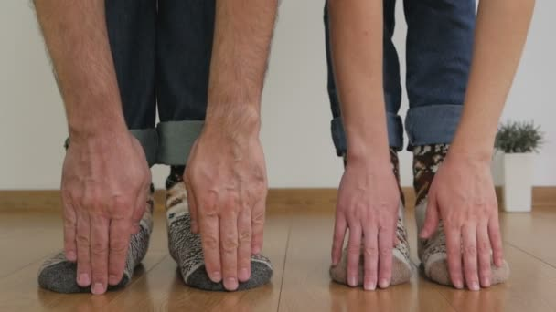 A man and a woman in warm woolen socks, doing gymnastics, bend over, touching the floor with their fingers.