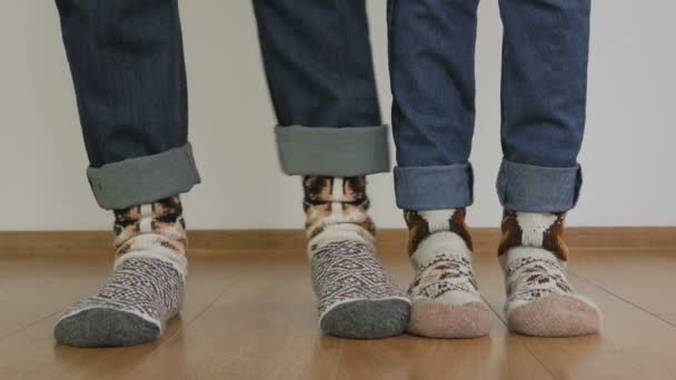 Closeup of legs of a man and woman dressed in warm knitted wool socks. A woman hurts her partner on the leg.
