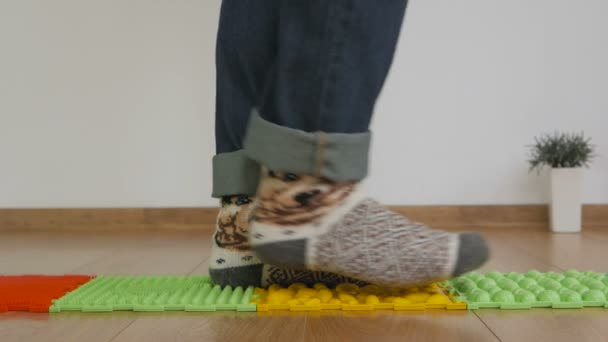 Close-up of the feet of a person wearing warm knitted wool socks, walking on an orthopedic studded rug.