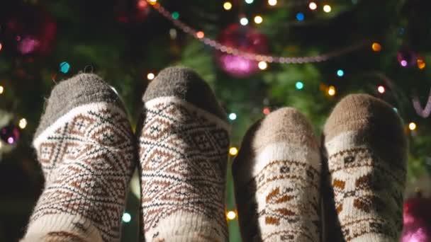 Zwei Beinpaare in warmen Wollsocken neben einen schönen Weihnachtsbaum