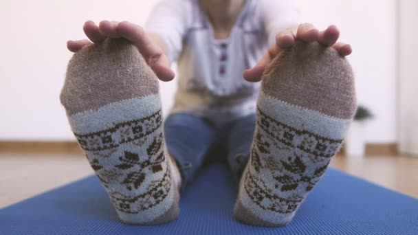 A woman in warm knitted socks does morning exercises, while sitting stretches her fingers up to her toes.