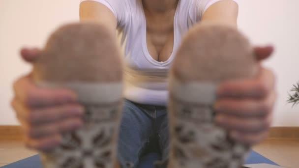 Una donna in calzini lavorati a maglia caldi fa esercizi di mattina, mentre seduta allunga dita fino le dita dei piedi.