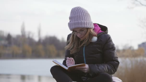 A young girl in glasses and a pink hat sitting by the river on a spring afternoon takes notes with a pen in a notebook